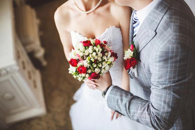 Noiva e noivo segurando um buquê de casamento