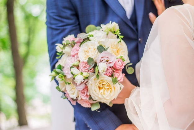 Noiva e noivo segurando um lindo buquê de flores.
