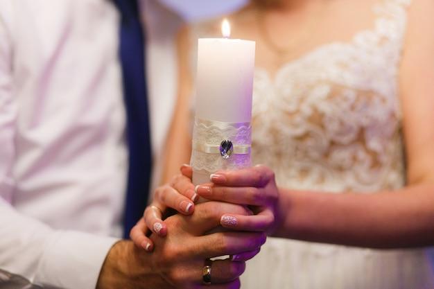 Noiva e noivo segurando vela. close-up, tiro, de, mãos