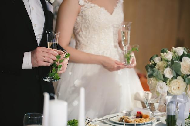 Noiva e noivo segurar copos de cristal cheios de champanhe