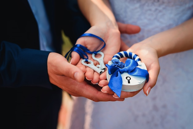 Noiva e noivo segurar um cadeado e chaves. tradição russa do casamento para consolidar o relacionamento Foto Premium