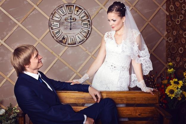 Noiva e noivo sentado em um banco em estúdio com interior vintage