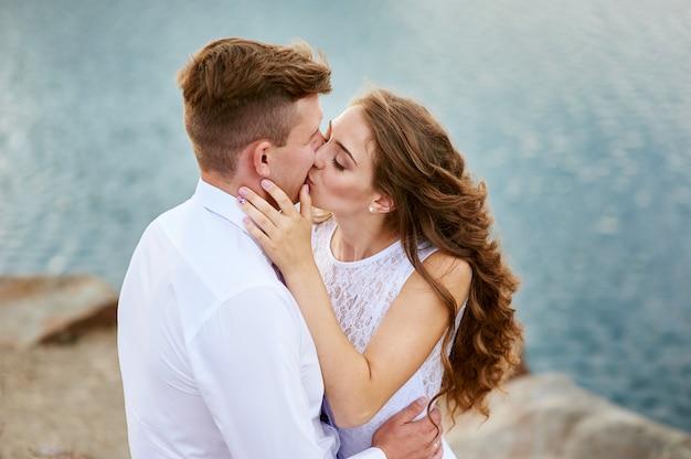 Noiva e noivo sentado na praia e beijando