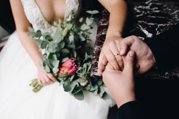 Noiva e noivo sentados juntos de mãos dadas