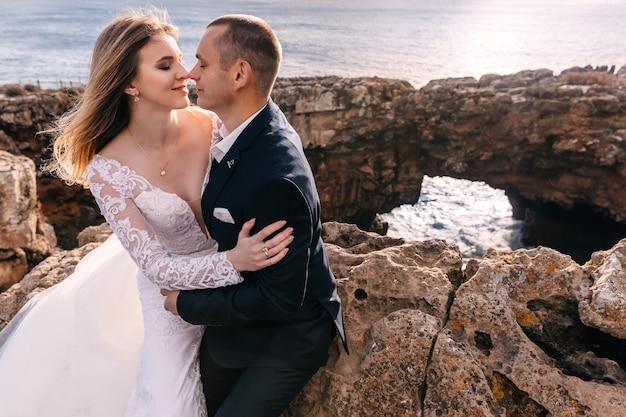 Noiva e noivo sentados nas pedras e fechando os olhos