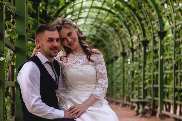 Noiva e noivo sentam-se abraçando no parque com um vinhedo artificial no fundo. recém-casados em vestidos de noiva no dia de casamento ensolarado. casal na rua em uma vista incrível. recém-casados apaixonados felizes juntos