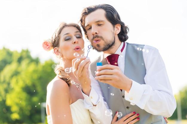 Noiva e noivo soprando bolhas fora no campo