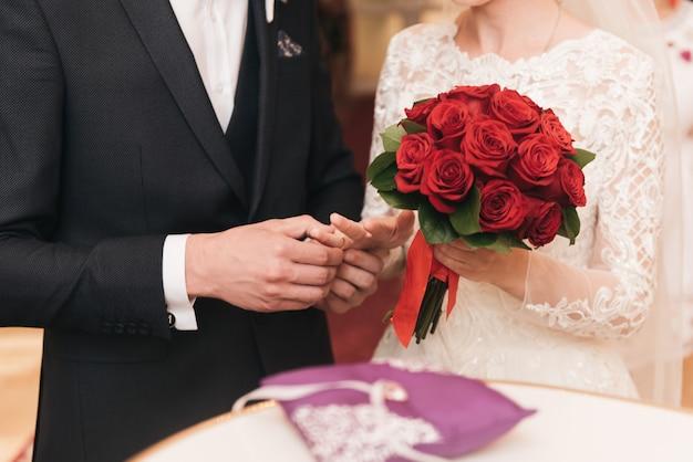 Noiva e noivo trocando alianças