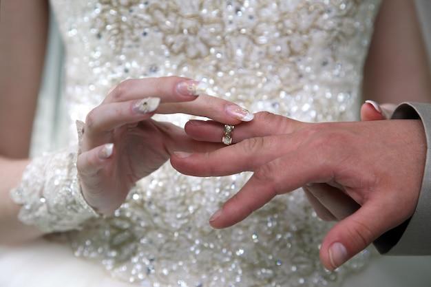 Noiva e noivo usam anéis de casamento um no outro