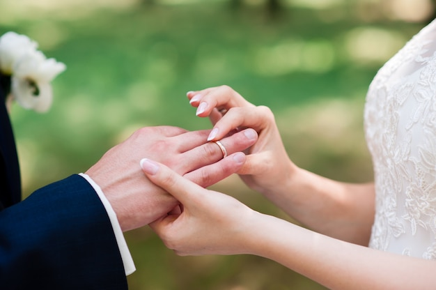 Noiva e noivo usam anéis