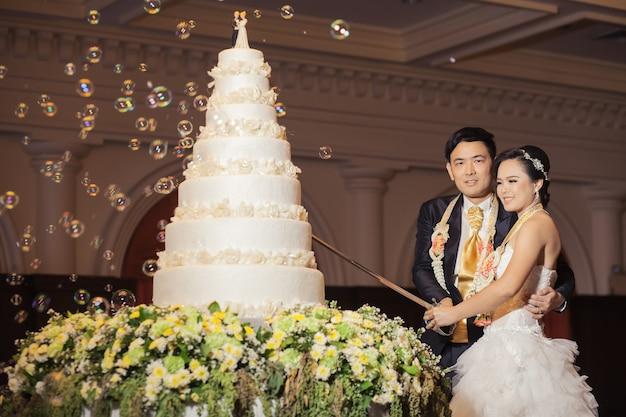 Noiva e o noivo estão cortando o bolo para comemoração no dia do casamento