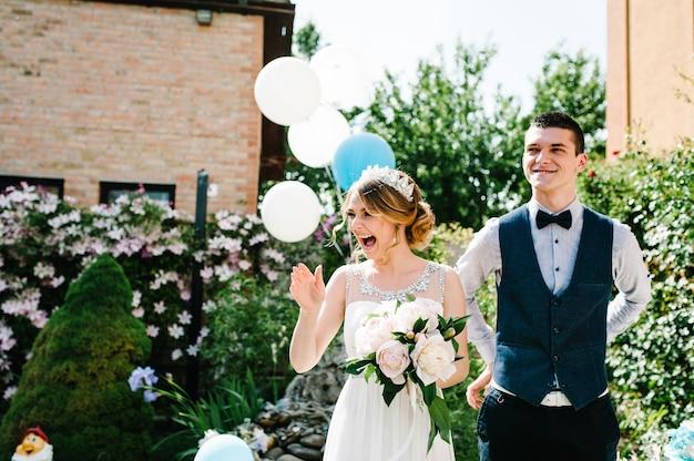 Noiva elegante e feliz com um buquê de peônias e o noivo de mãos dadas