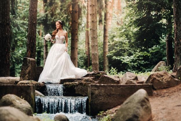 Noiva elegante em um vestido branco e luvas segurando um buquê fica perto de um riacho na floresta