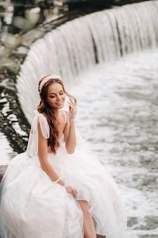 Noiva elegante em um vestido branco, luvas e pés descalços está sentada perto de uma cachoeira no parque apreciando a natureza.