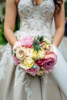 Noiva elegante em um vestido branco mantém um close de buquê de casamento incomum. buquê de casamento delicado de diferentes flores nas mãos da noiva,
