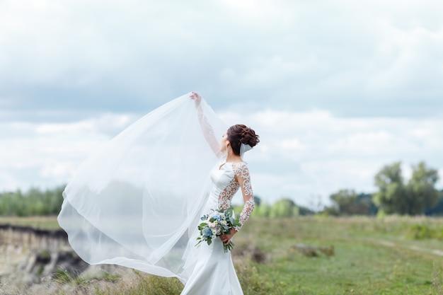 Noiva elegante em um vestido de noiva com laço segurando o buquê de flores