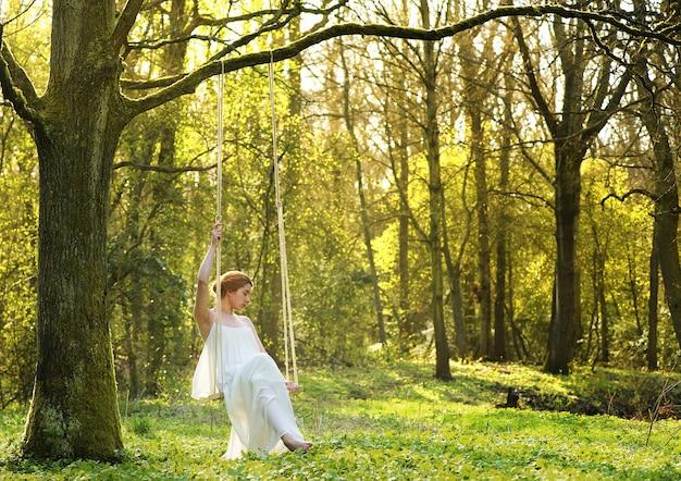 Noiva elegante em vestido de noiva branco sentado sozinho no balanço ao ar livre