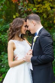Noiva elegante encaracolada e noivo elegante se abraçando em um fundo verde bonito