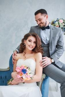 Noiva em lindo vestido e noivo de terno cinza, sentado no sofá dentro de casa. estilo de casamento na moda