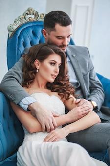 Noiva em lindo vestido e noivo de terno cinza, sentado no sofá dentro de casa