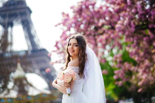 Noiva em paris, vestido branco, segurando um buquê