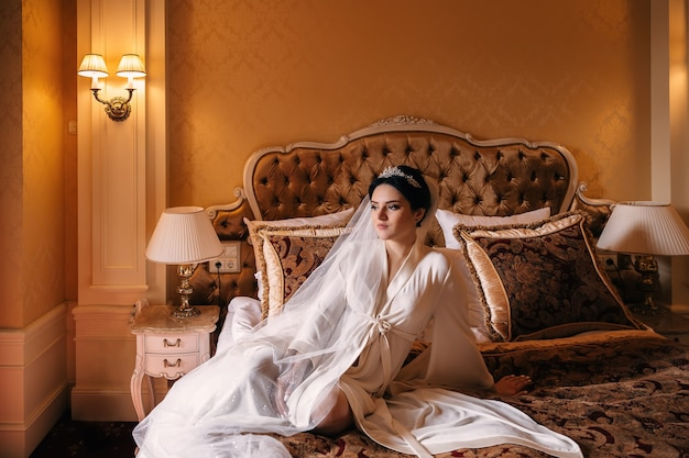 Noiva em roupão branco e véu de noiva, sentada na cama chique. lindo quarto clássico.