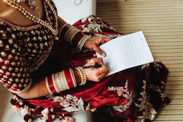 Noiva em roupas tradicionais indianas está escrevendo seus votos no papel
