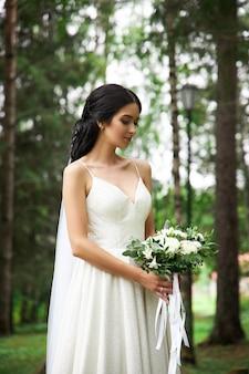 Noiva em um lindo vestido branco com um buquê de flores