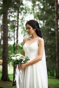 Noiva em um lindo vestido branco e um buquê de flores nas mãos está esperando para a cerimônia de casamento. mulher bonita com um buquê de casamento nas mãos