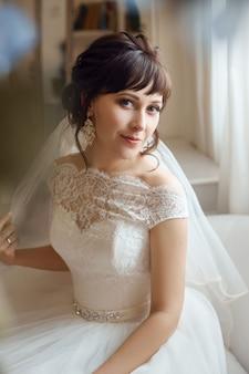 Noiva em um lindo vestido branco se prepara para a cerimônia de casamento. manhã da noiva