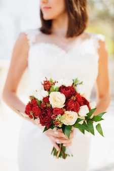 Noiva em um lindo vestido branco segurando um buquê de rosas vermelhas e rosa nas mãos