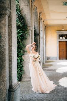 Noiva em um lindo vestido com um buquê de flores rosa parada no corredor abobadado com a mão
