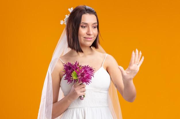 Noiva em um lindo vestido de noiva com buquê de flores olhando para o anel em seu dedo em pé sobre uma parede laranja