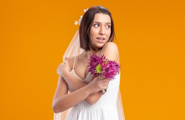 Noiva em um lindo vestido de noiva com buquê de flores olhando para o lado sorrindo alegremente