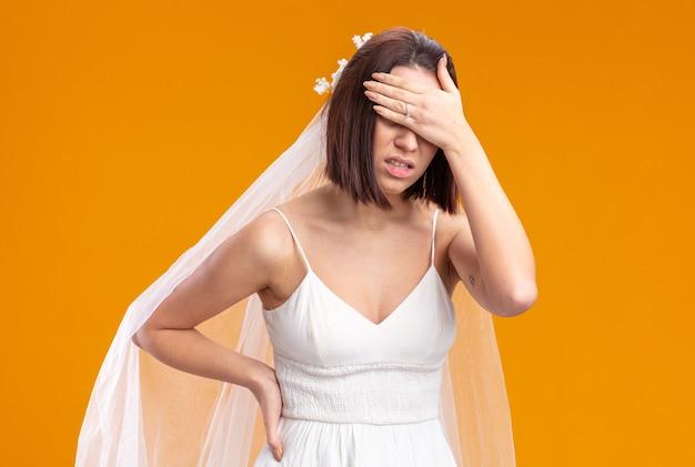 Noiva em um lindo vestido de noiva parecendo doente, cobrindo os olhos com a mão em pé sobre a parede laranja