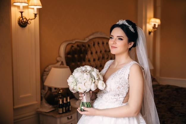Noiva em um lindo vestido de noiva segura um buquê de casamento e olha para a câmera. noiva em um fundo de um quarto aconchegante.