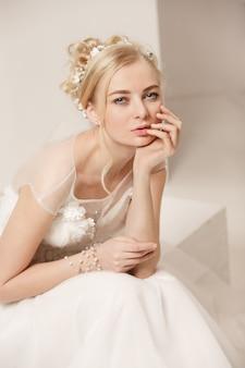 Noiva em um lindo vestido de pé dentro de casa no interior do estúdio branco como em casa.
