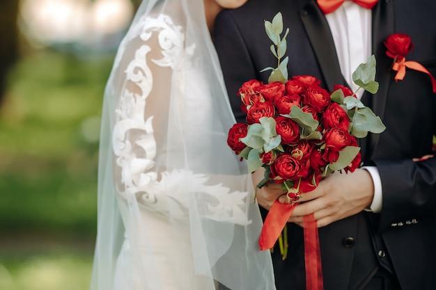 Noiva em um lindo vestido e noivo segurando um buquê de flores