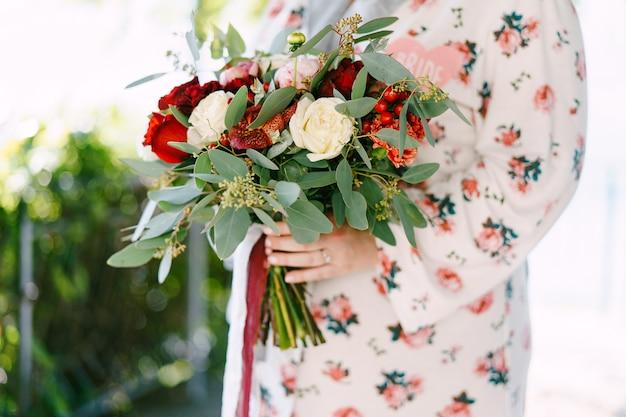 Noiva em um roupão de banho com um buquê de flores em pé na varanda, close-up