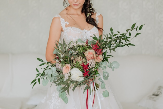 Noiva em um vestido branco com um buquê de luxo decorado com eucalipto