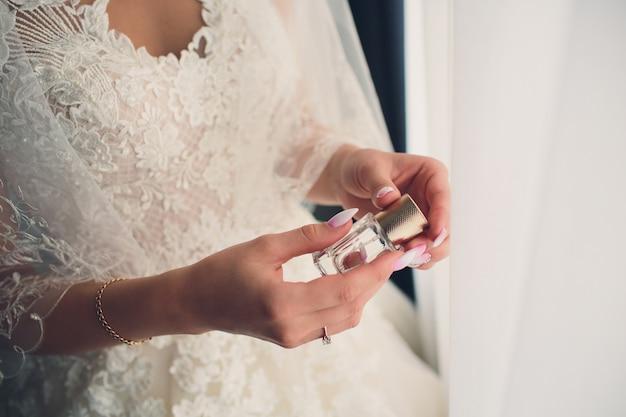 Noiva em um vestido branco com uma manicure francesa pastel segura na mão um frasco de perfume.