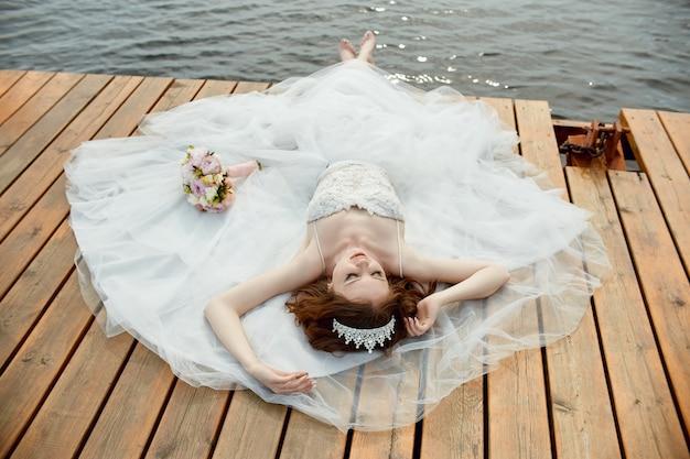 Noiva em um vestido branco fica na ponte e olha para o lago. mulher em um vestido de noiva com um buquê de flores