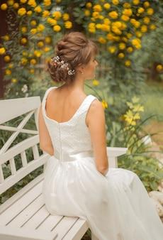 Noiva em um vestido branco, sentada no banco do parque atrás das flores. conceito de casamento feliz.