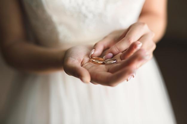 Noiva em um vestido branco tem alianças de casamento em suas mãos