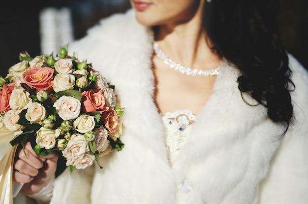 Noiva em um vestido de noiva e um casaco branco segurando uma bela nós