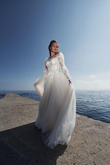 Noiva em um vestido de noiva na praia à beira-mar no céu azul