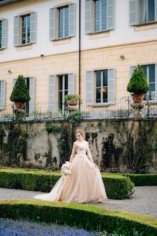 Noiva em um vestido rosa com um buquê de flores caminha pelo parque, passando pelos arbustos aparados de