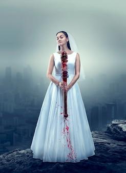 Noiva em vestido de noiva branco com morcego ensanguentado