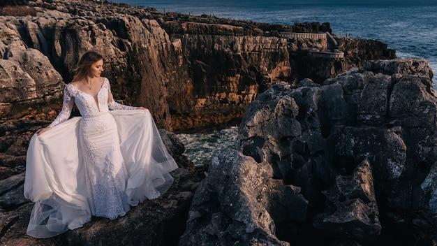 Noiva em vestido de noiva branco fechou os olhos no fundo das rochas e do mar