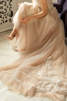 Noiva em vestido de noiva de luxo e sapatos de salto alto